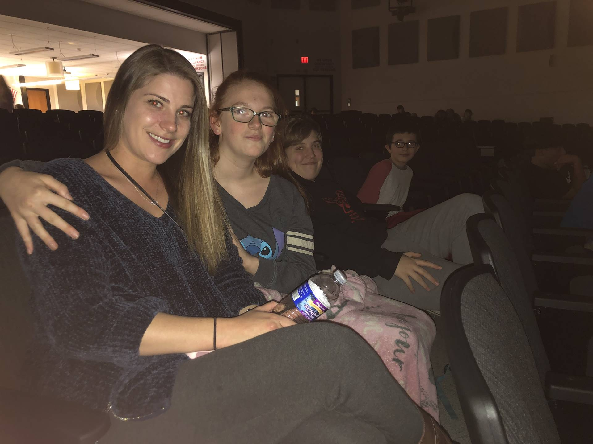 A group of middle school students sitting in auditorium seats with a woman