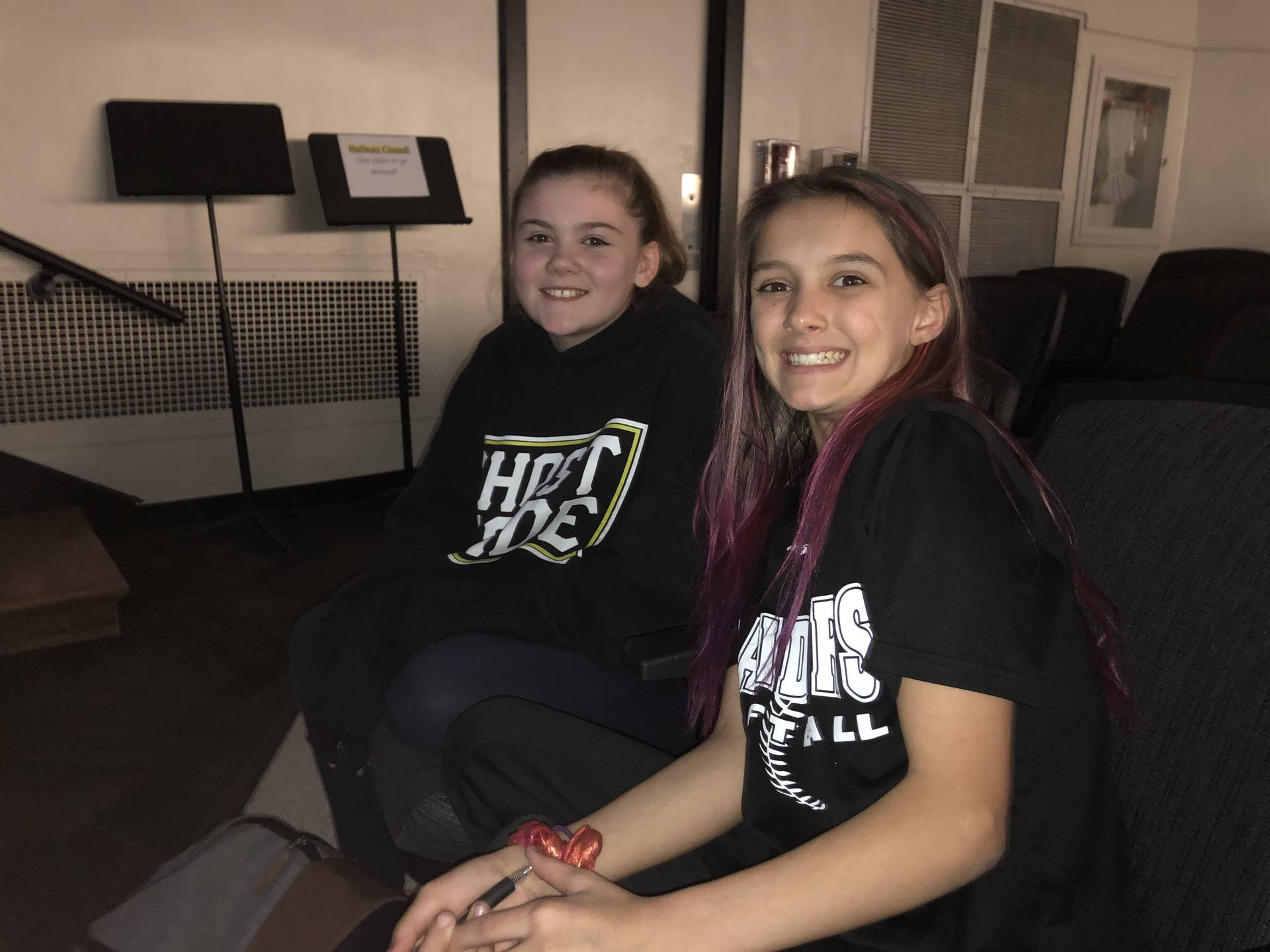 Two girls sitting in auditorium seats