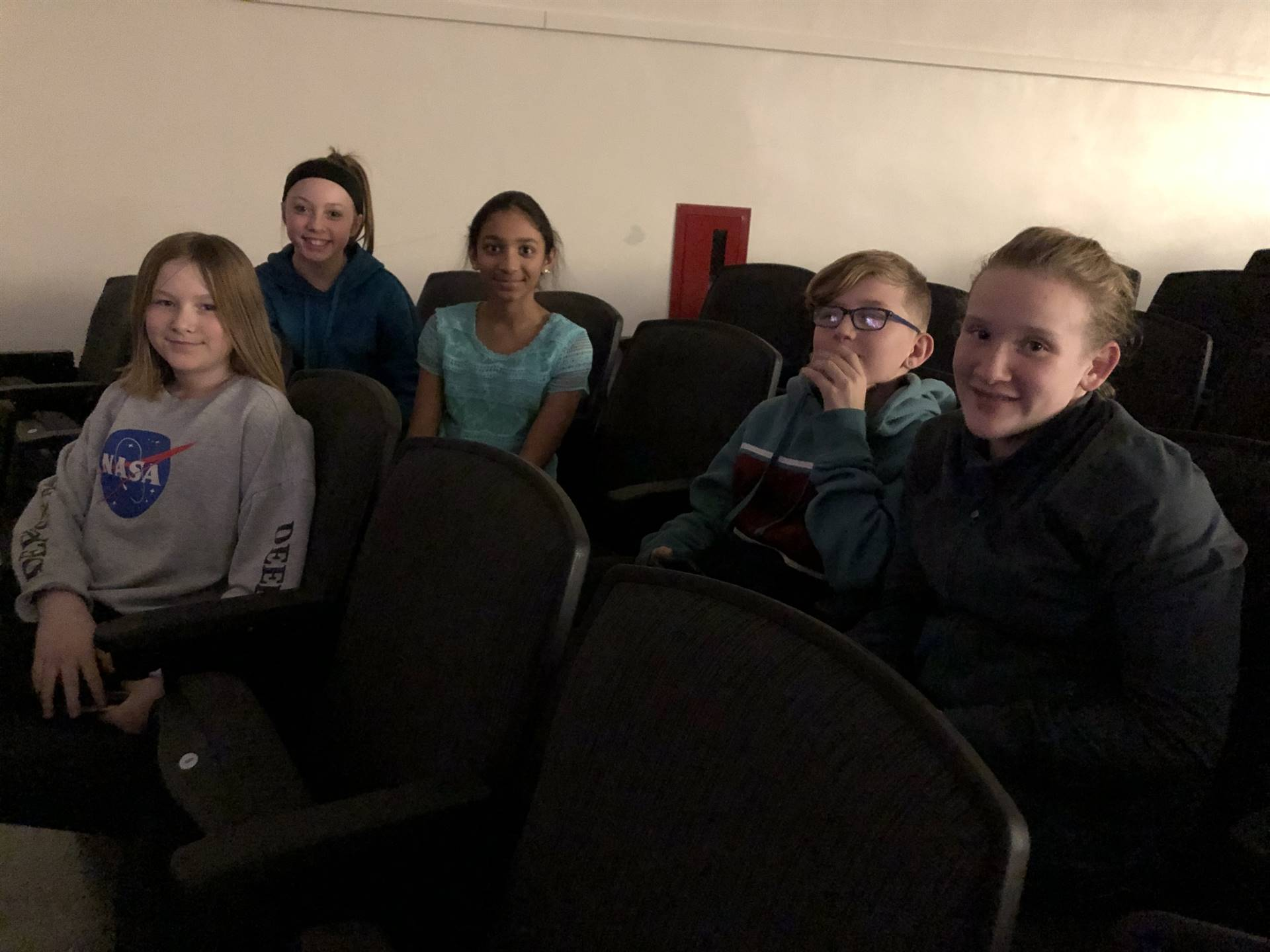 A group of middle school students sitting in auditorium seats