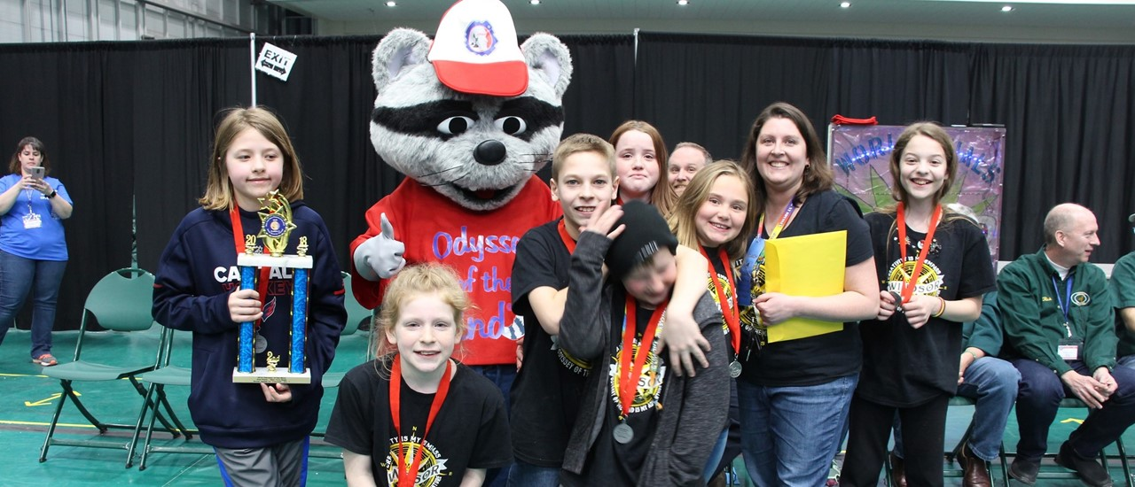 A group of elementary students, one holding a trophy, standing with a mascot