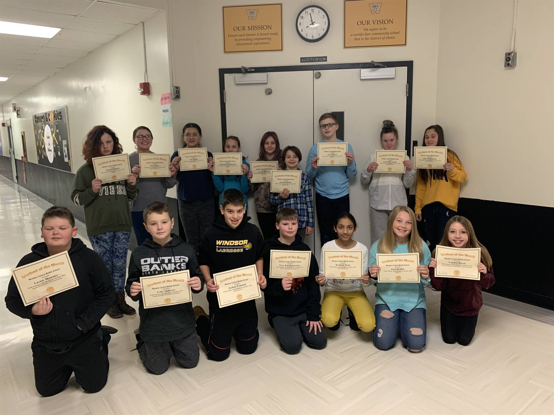 16 students holding certificates in a hallway