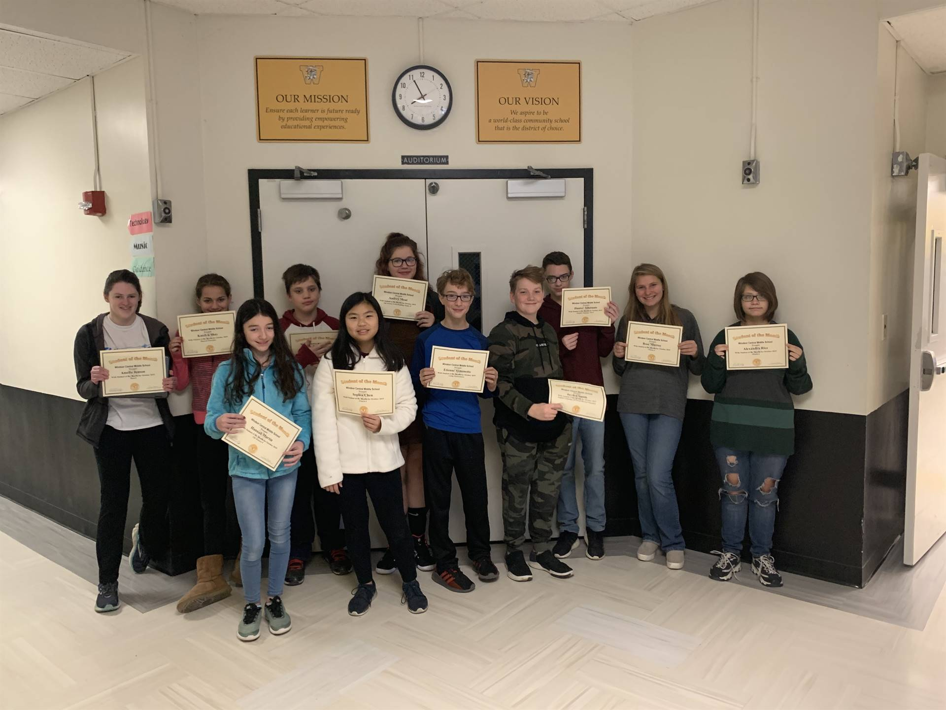 11 students holding certificates in a hallway