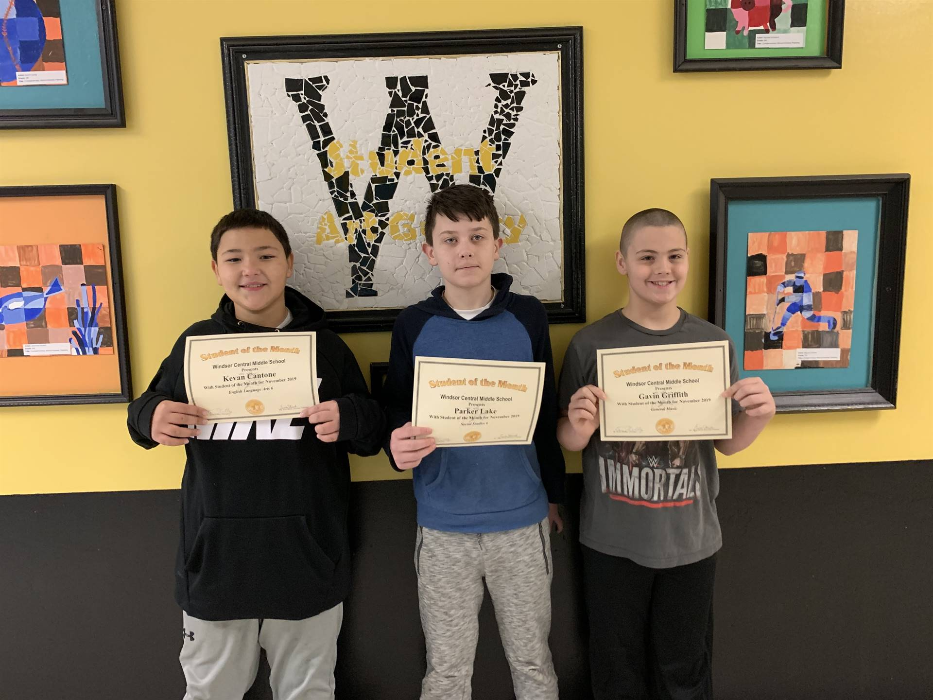 Three students holding certificates in front of a wall
