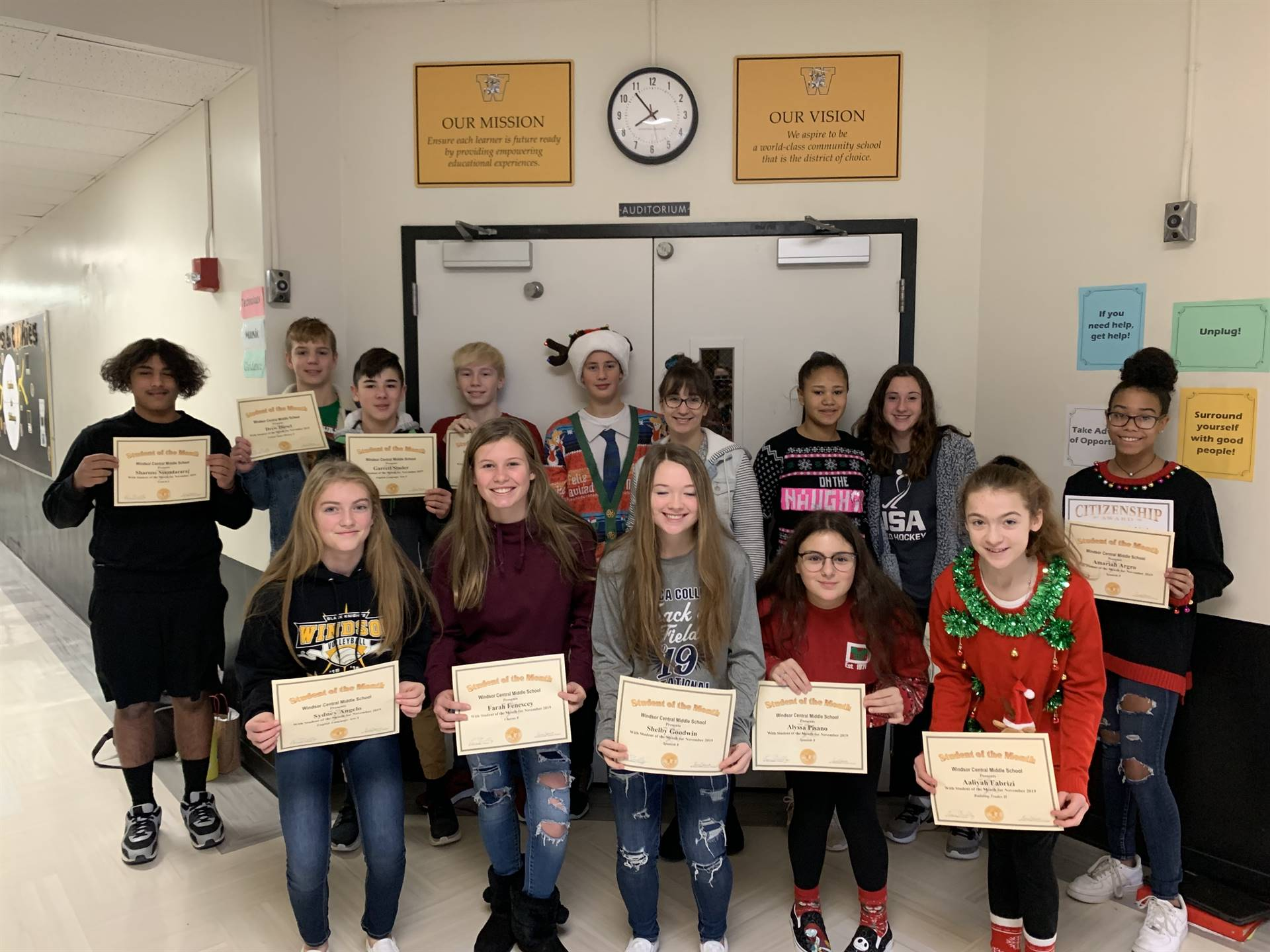 Two rows of 8th grade students holding certificates in a hallway
