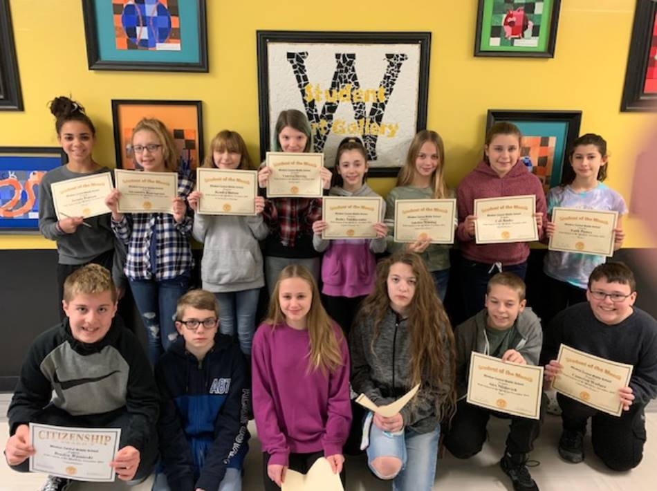 Two rows of 7th grade students holding certificates in front of a wall