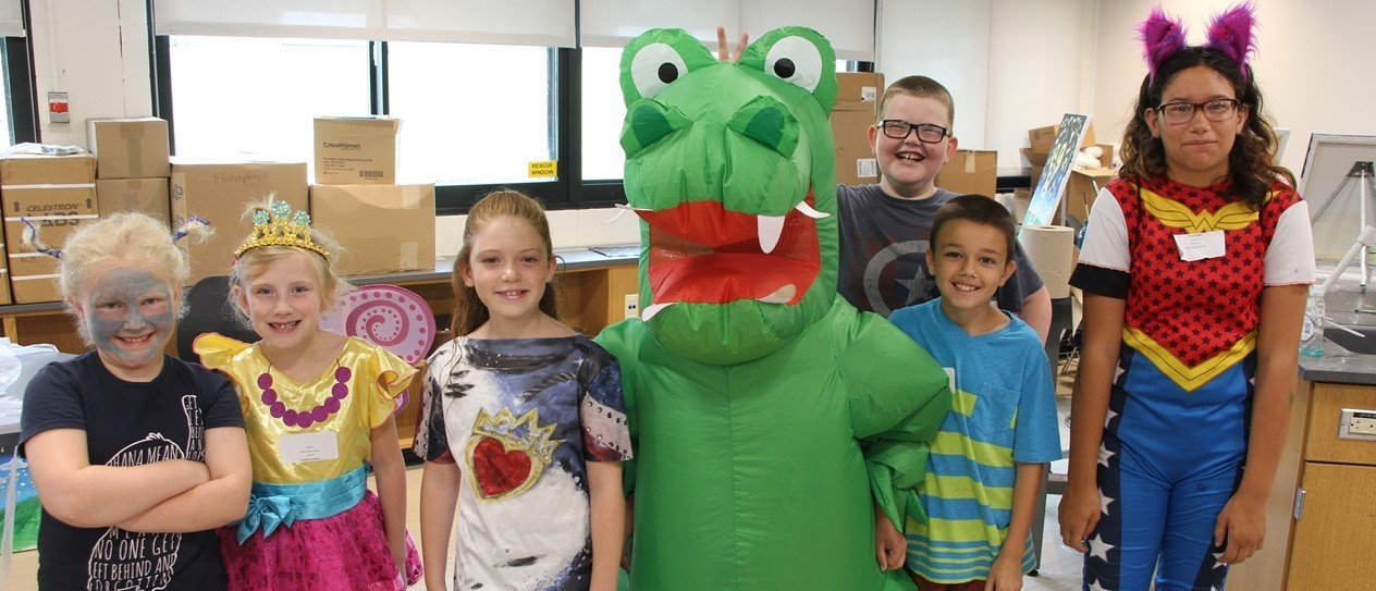 Six young children standing with a child in a green alligator costume