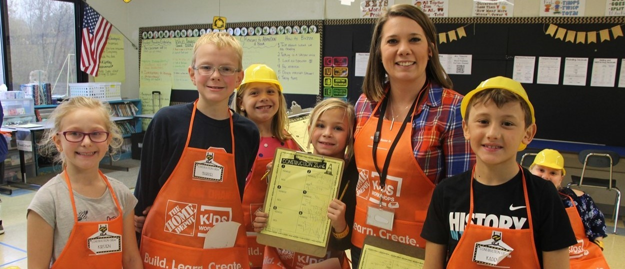 A woman and five young children in Home Depot orange aprons