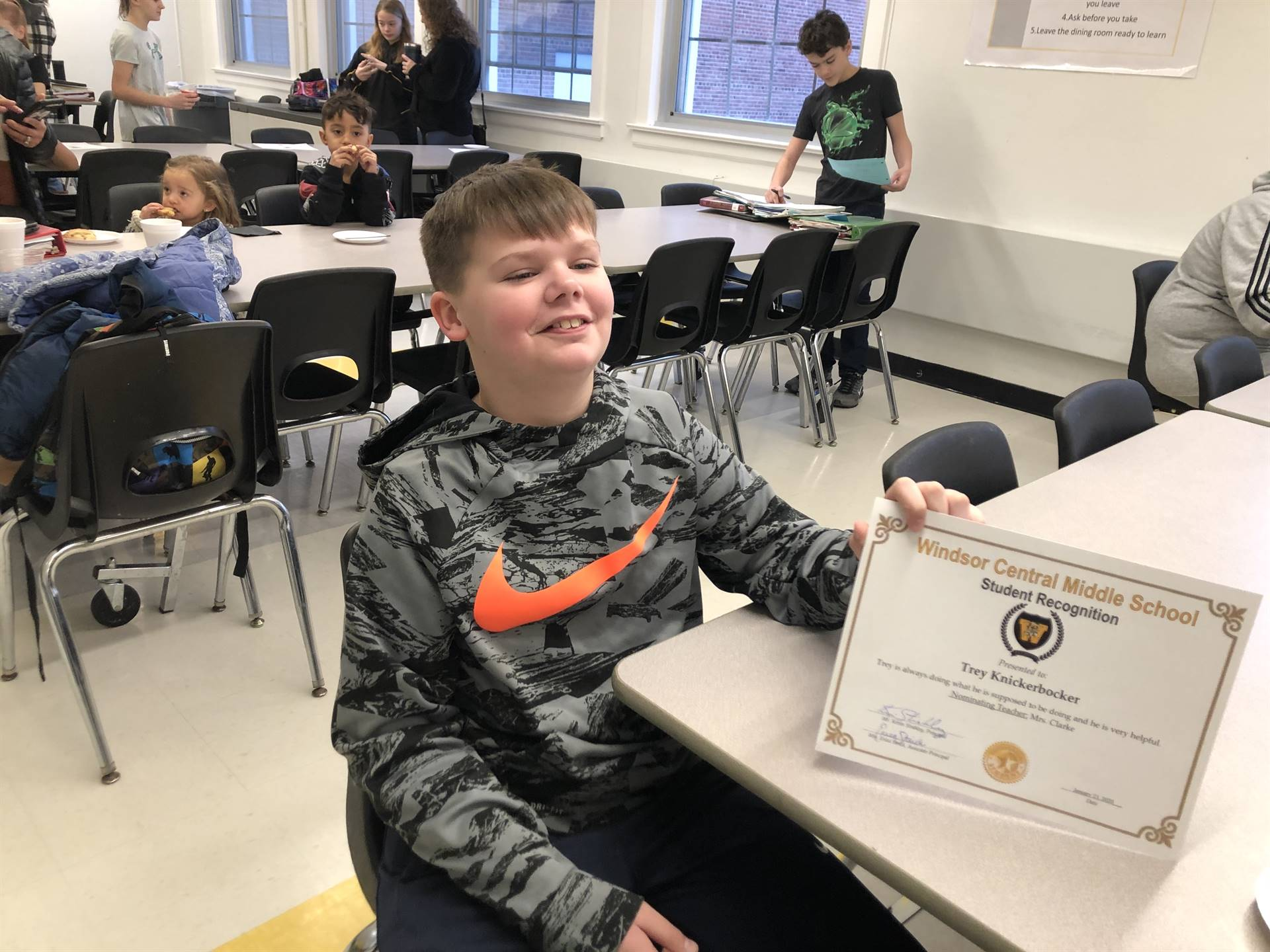 A boy sitting, holding a certificate