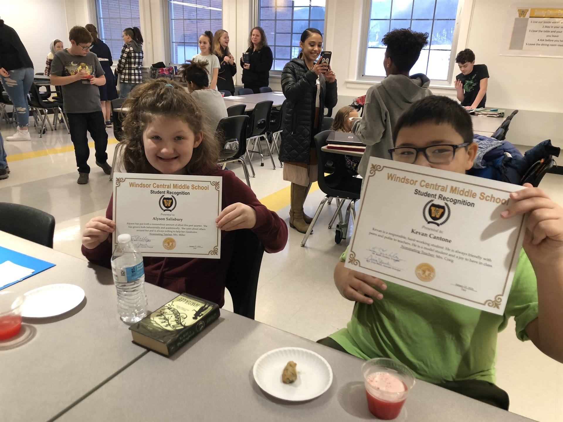 Two children sitting, holding certificates