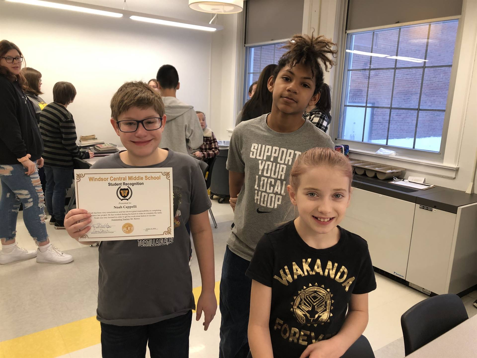 Two boys, one holding a certificate, and a girl standing
