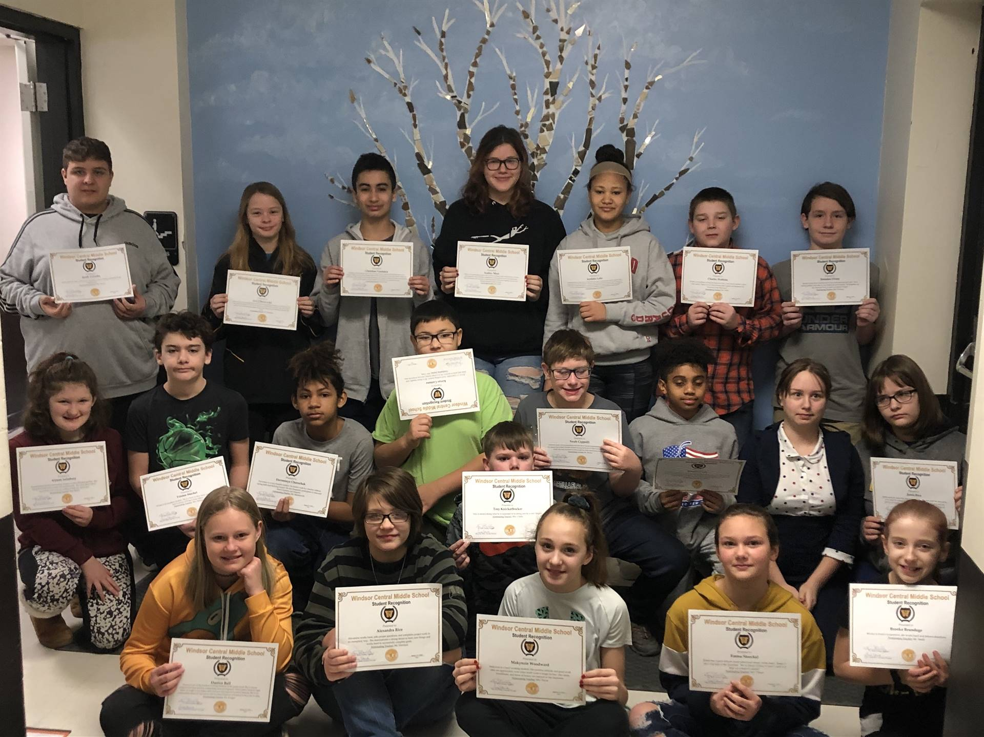 Three rows of children holding certificates