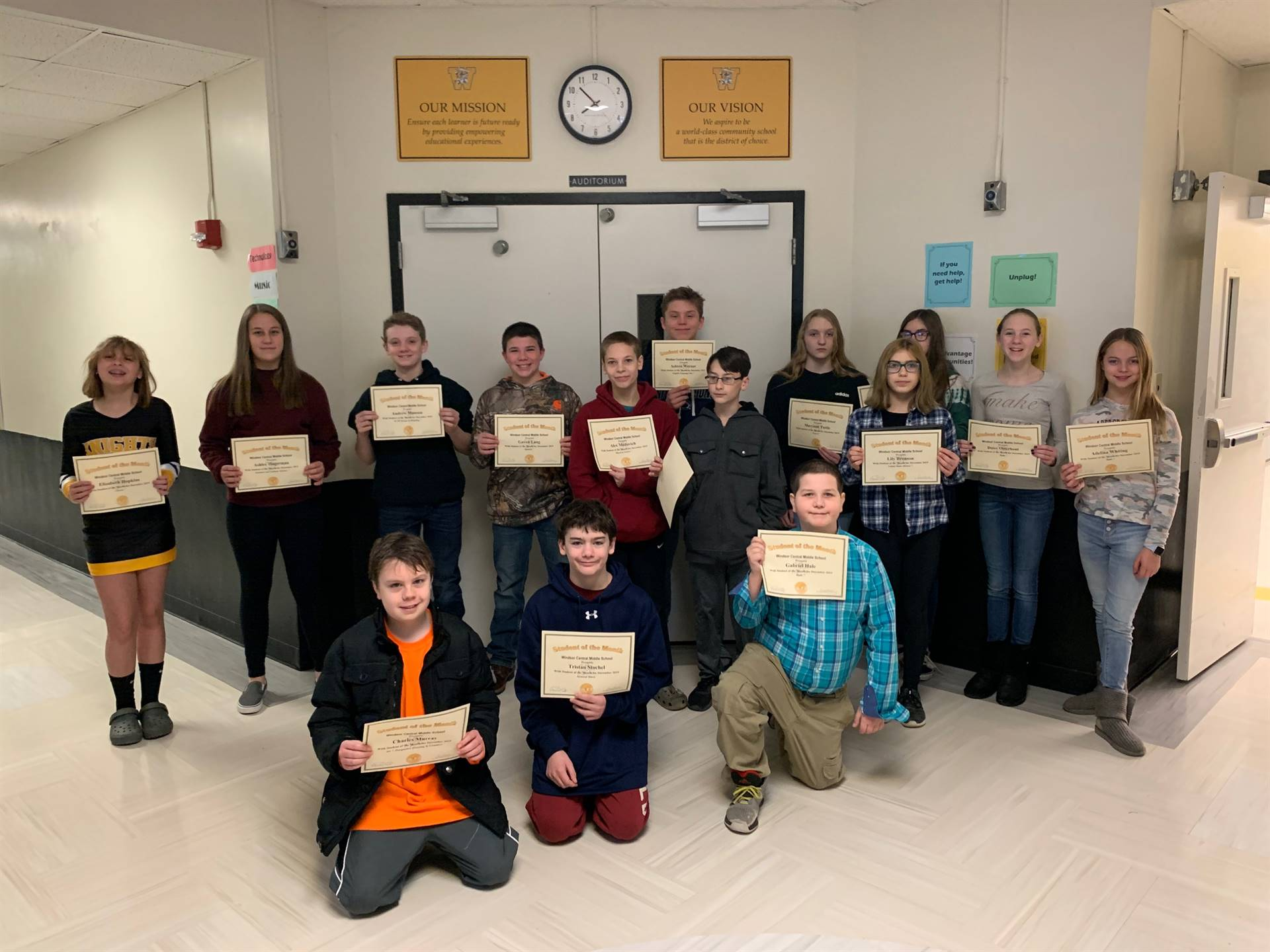 Two rows of young students holding certificates