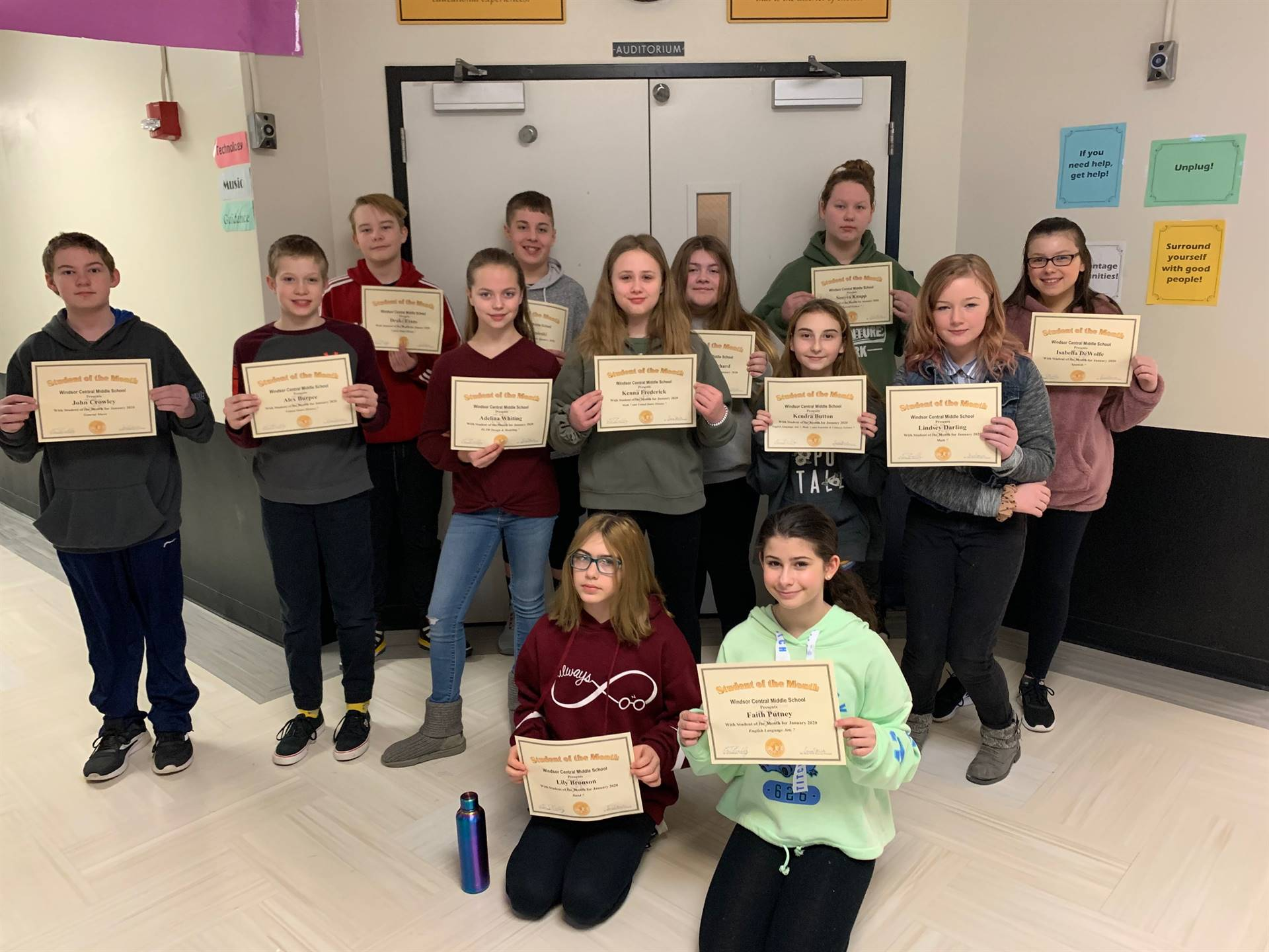 Three rows of 7th grade students holding certificates