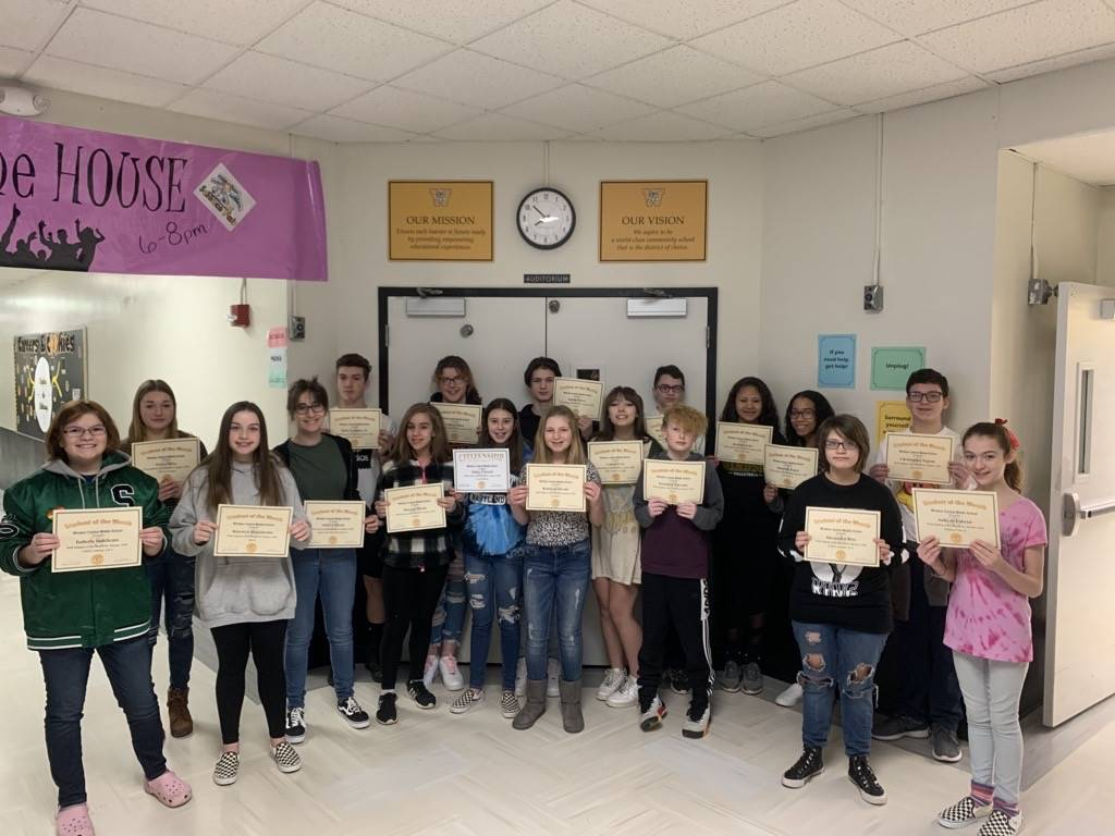 18 8th grade students standing in a hallway holding certificates