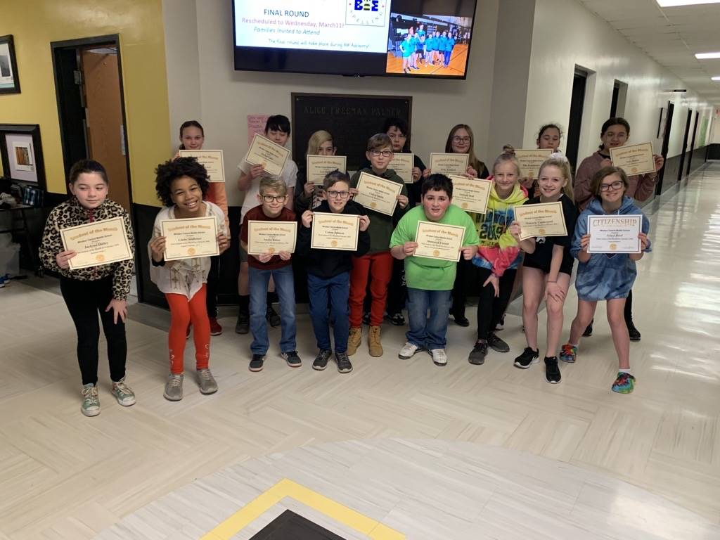 2 Rows of boys and girls holding certificates while standing in a school hallway