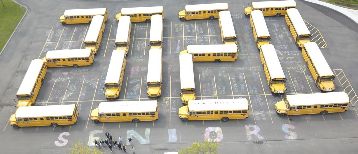 "Buses parked in a lot, spelling ""2020"""