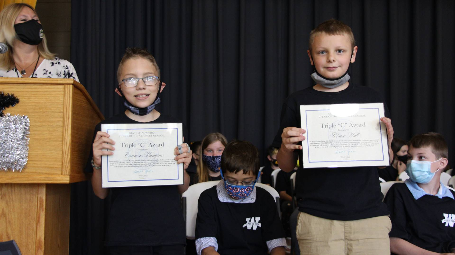 Two young students holding certificates