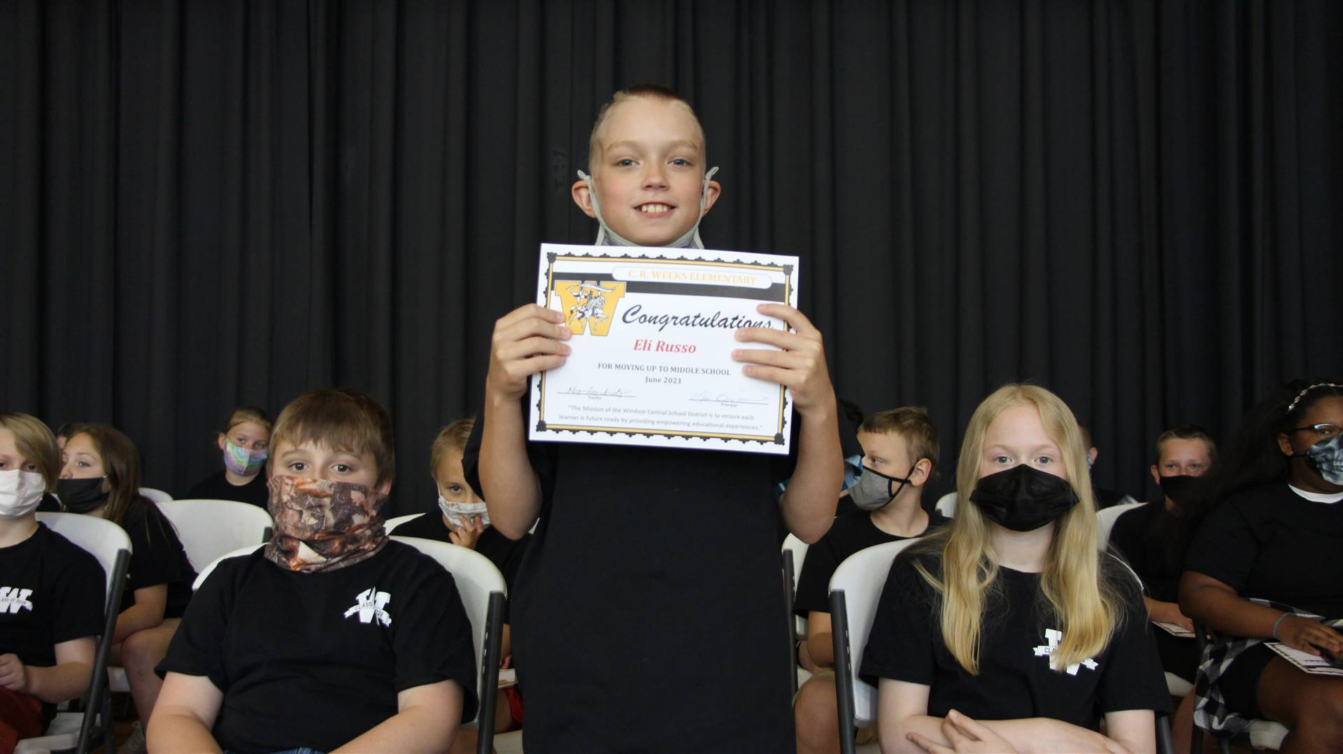 Young boy holding a certificate
